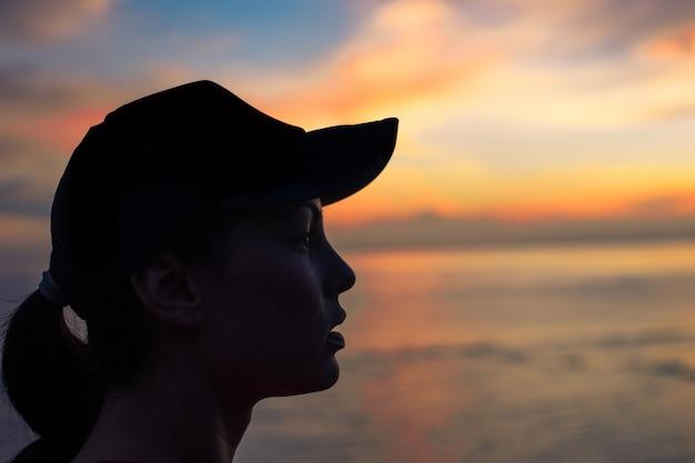 Silhueta de uma mulher sentada na praia