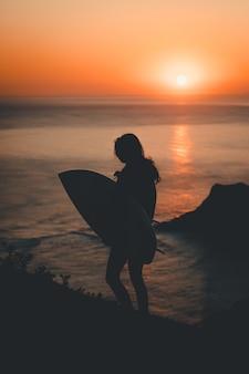 Silhueta de uma mulher solitária segurando uma prancha de surf, caminhando à beira-mar ao pôr do sol
