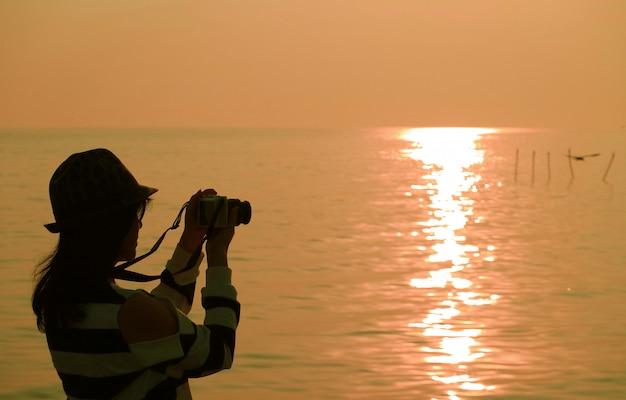 Silhueta de uma mulher tirando fotos no sol nascente à beira-mar