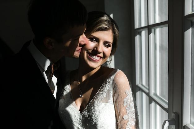 Silhueta de uma noiva e do noivo ao lado da janela.