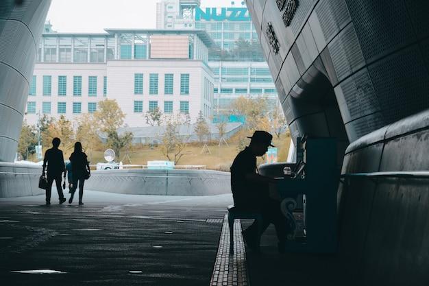 Silhueta de uma pessoa com um chapéu tocando piano ao ar livre e pessoas andando por