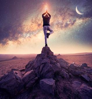 Silhueta de uma pessoa em posição de árvore de ioga em uma rocha com a via láctea e a lua de fundo