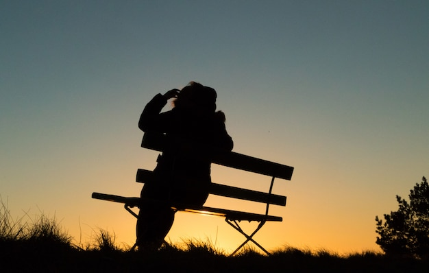 Silhueta de uma pessoa sentada em um banco no pôr do sol