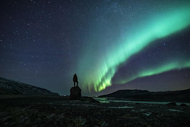 Silhueta de uma pessoa sob a aurora boreal