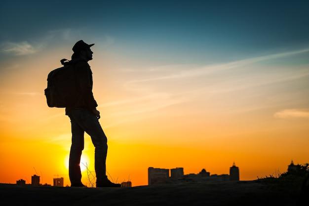 Silhueta de viajante assistindo incrível pôr do sol. jovem casual com mochila e chapéu de cowboy sozinho na colina acima da paisagem urbana à noite. plano de fundo ao ar livre do conceito de viagens de estilo de vida. kiev, ucrânia