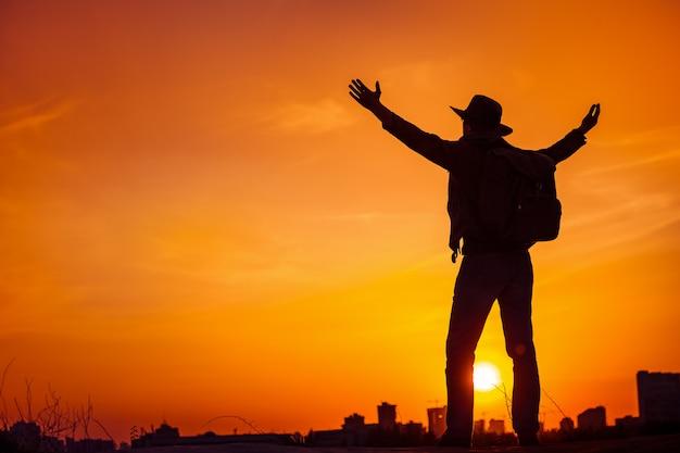 Silhueta de viajante, desfrutando de liberdade, vitória, sucesso.