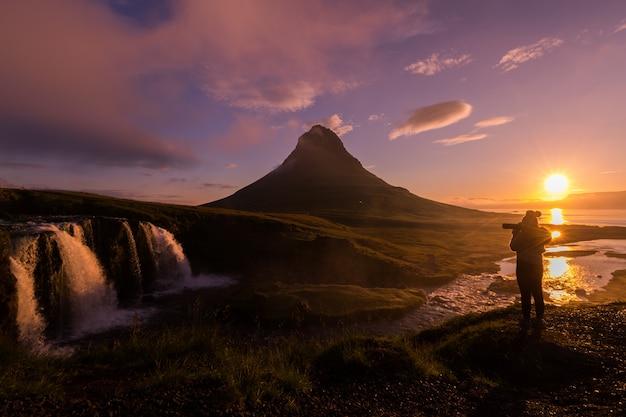 Silhueta de vista panorâmica do fotógrafo tirando foto kirkjufellsfoss na manhã