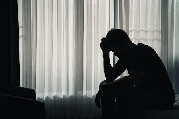 Silhueta deprimida tristemente sentada na cama no quarto, conceito de depressão