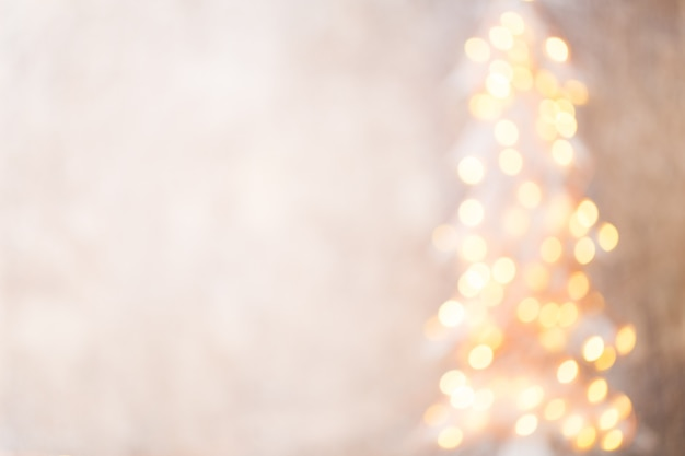 Silhueta desfocada da árvore de natal com luzes desfocadas.