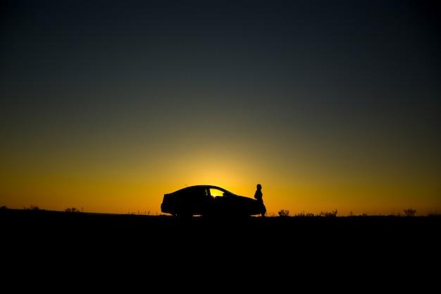Silhueta do carro sedan no fundo por do sol lindo