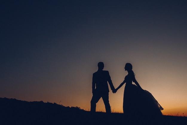 Silhueta do casal de noivos, o noivo e a noiva de mãos dadas no fundo da sunse