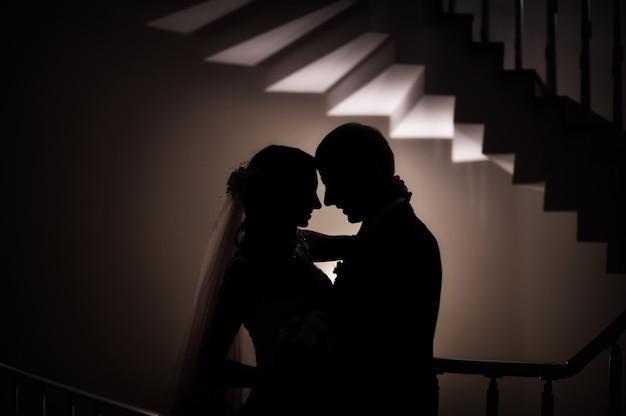 Silhueta do casamento a noiva e o noivo amam