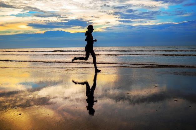 Silhueta do corredor de mulher correndo na praia do sol, fitness e conceito de vida saudável