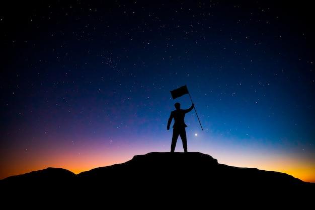 Silhueta do empresário com bandeira no topo da montanha sobre estrelas preenche o fundo do céu, negócios, sucesso, liderança e conceito de realização
