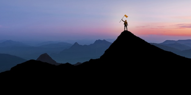 Silhueta do empresário em pé no topo da montanha sobre fundo crepúsculo do sol com o conceito de bandeira, vencedor, sucesso e liderança