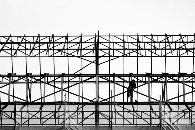 Silhueta do engenheiro em pé para trabalhar com segurança na alta estrutura do edifício