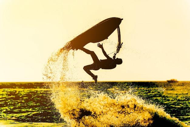Silhueta do esqui do jato do estilo livre da movimentação do homem no por do sol o cavaleiro profissional faz truques no mar.