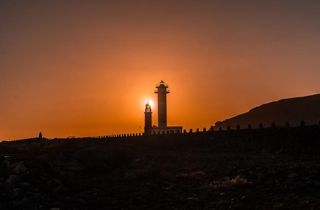 Silhueta do farol de fuencaliente ao pôr do sol, na rota dos vulcões ao sul da ilha de la palma, nas ilhas canárias, espanha