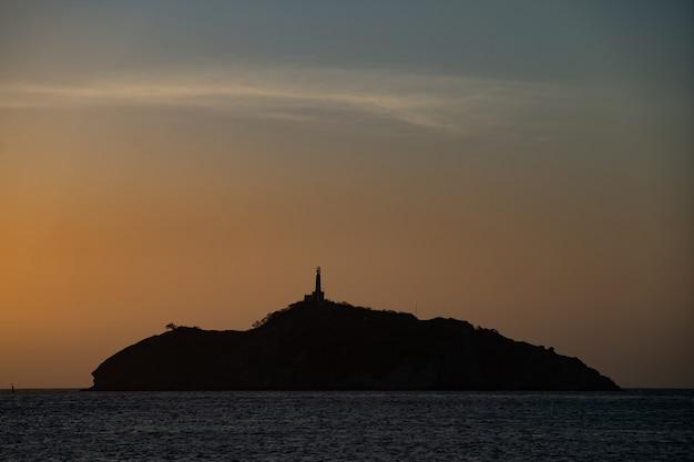 Silhueta do farol no topo de uma pequena ilha rochosa no conceito de mar de viagem e aventura