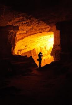 Silhueta do fotógrafo em uma caverna