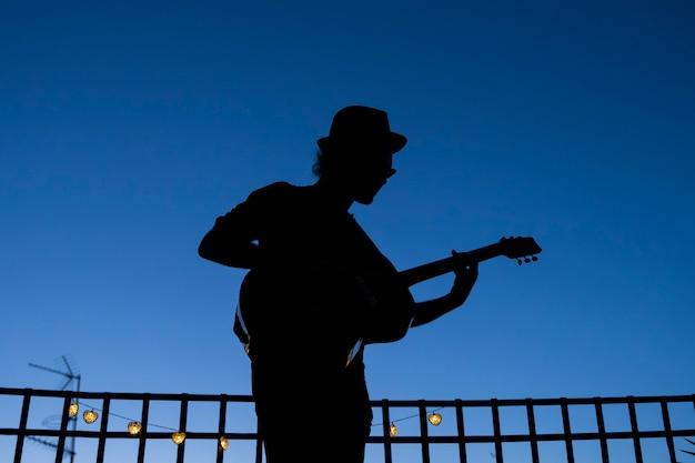 Silhueta do guitarrista de homem tocando um violão