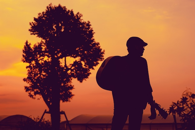 Silhueta do guitarrista em pé, olhando para o sucesso, conceito de silhueta