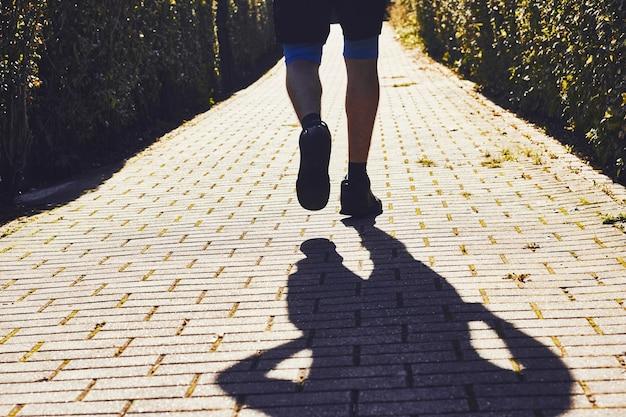 Silhueta do homem atleta, movimentando-se no parque sity de manhã