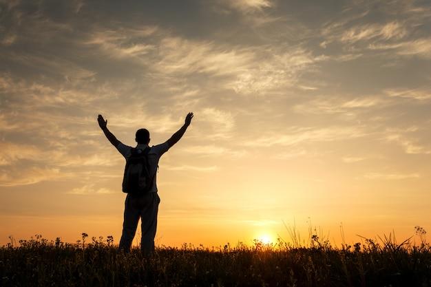 Silhueta do homem com os braços levantados e lindo céu
