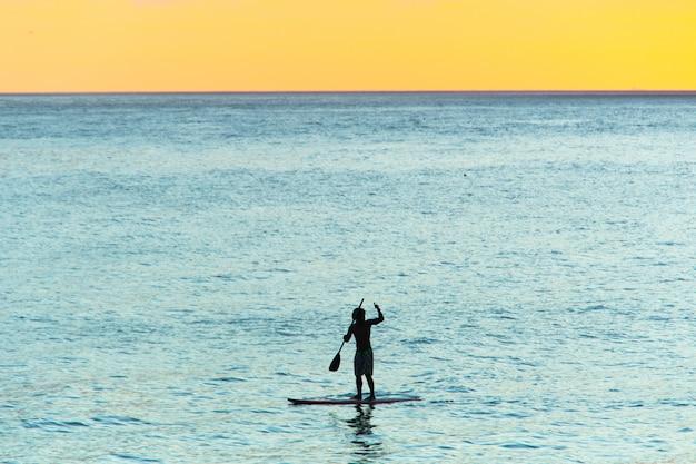 Silhueta do homem com seu stand up paddle com um belo pôr do sol
