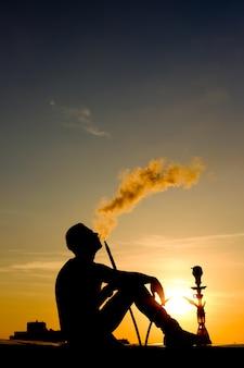 Silhueta do homem fumar cachimbo de água sentado no telhado no pôr do sol