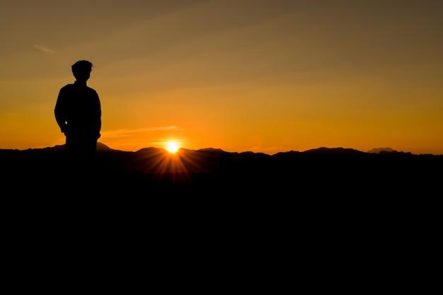 Silhueta do homem no por do sol, curso das férias da liberdade do estilo de vida do conceito.