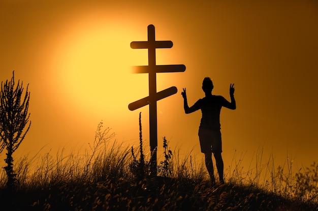 Silhueta do homem perto da cruz ortodoxa do pôr do sol.
