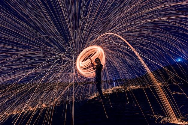 Silhueta do homem que faz um círculo de faíscas durante a noite