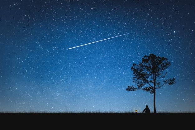 Silhueta do homem que senta-se na montanha e no céu noturno com estrela de tiro. conceito sozinho.