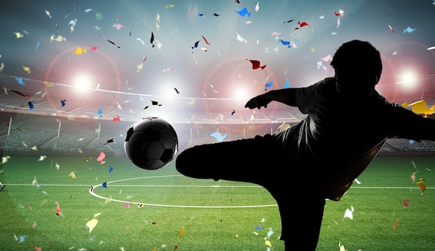Silhueta do jogador de futebol chutando a bola