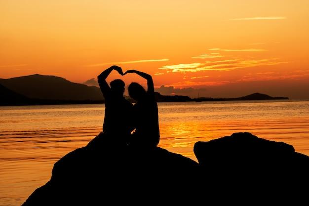 Silhueta do jovem casal apaixonado na praia, fundo por do sol