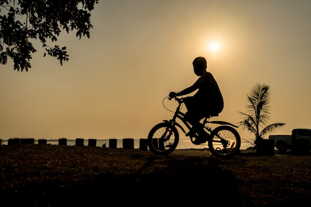 Silhueta do menino andando de bicicleta sob o pôr do sol perto da praia em suas férias