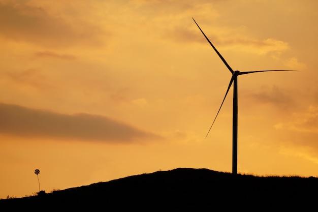 Silhueta do moinho de vento só em um monte na frente de um por do sol alaranjado brilhante.