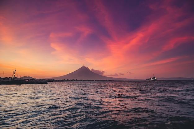 Silhueta do nascer do sol do oceano nas filipinas vulcão mayon em erupção nuvem neblina tropical ásia paisagem marinha