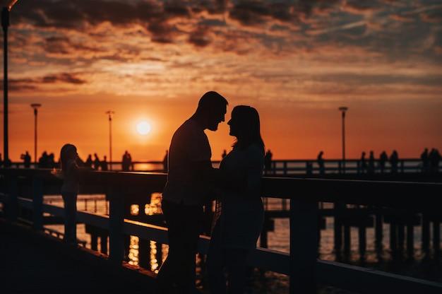 Silhueta do retrato de um lindo casal recém-casado. um homem amoroso abraça uma garota ao pôr do sol, no contexto do mar parado no cais.