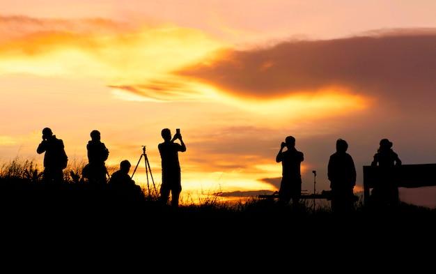 Silhueta do viajante que toma a imagem da paisagem durante o nascer do sol.