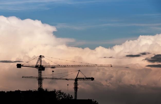 Silhueta dos guindastes de construção contra o céu com nuvens grandes.
