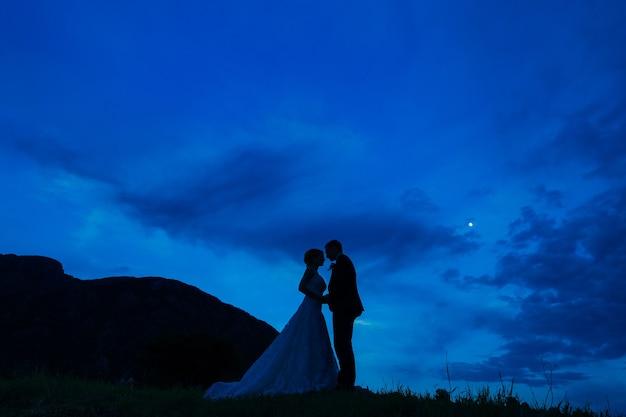 Silhueta dos recém-casados contra o céu no pôr do sol do casamento