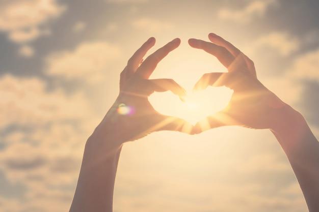Silhueta em forma de coração de mão feita contra o sol e o céu de um amanhecer ou pôr do sol