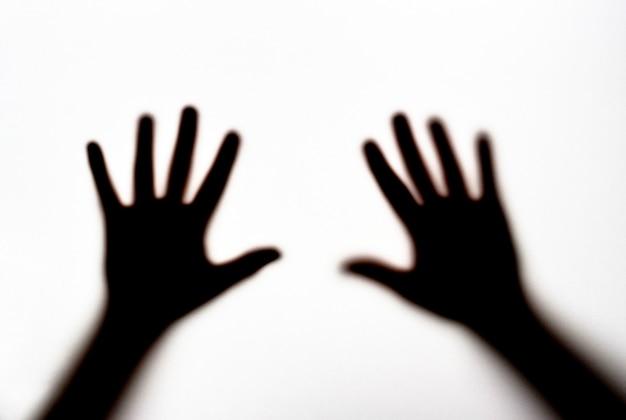 Silhueta escura das mãos femininas no fundo branco, conceito de medo