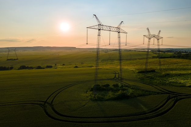 Silhueta escura de torres de alta tensão com linhas de energia elétrica ao nascer do sol.