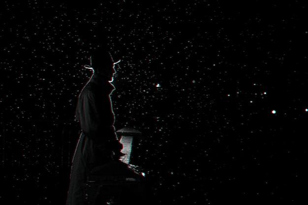 Silhueta escura de um homem com um chapéu à noite na chuva na cidade. preto e branco com efeito de realidade virtual de falha 3d
