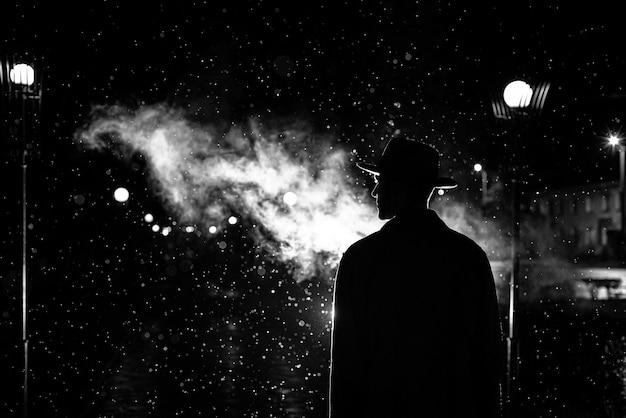 Silhueta escura de um homem com um chapéu na chuva em uma rua à noite em uma cidade no estilo de noir