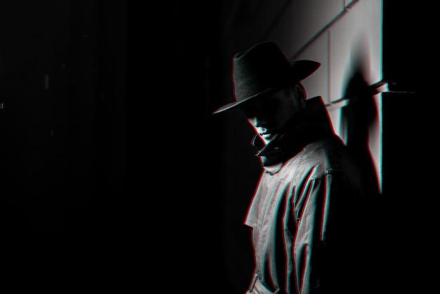 Silhueta escura de um homem com uma capa de chuva e um chapéu à noite. preto e branco com efeito de realidade virtual de falha 3d