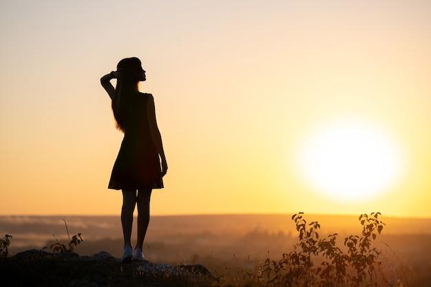 Silhueta escura de uma jovem mulher com vestido de verão em pé ao ar livre, apreciando a vista da natureza ao pôr do sol.